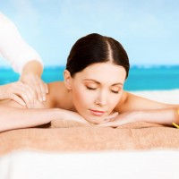 picture of woman in spa salon getting massage on the beach